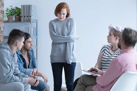 Woman with mental problem talking in front of support group Stock Photo