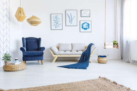White home interior with sofa, armchair, posters, lamps and rug Foto de archivo