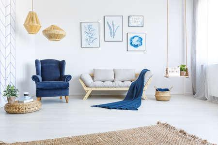Interni casa bianca con divano, poltrona, poster, lampade e tappeto