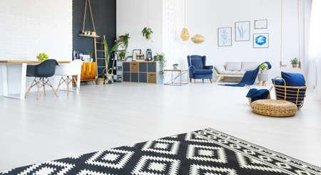 Modern, licht appartement met een woonkamer, een zwarte muur en tapijt