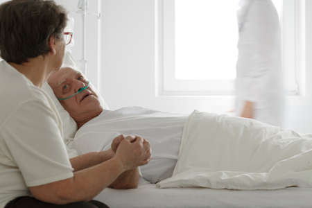 Dying man with nasal cannula and his worried supporting wife Stock Photo