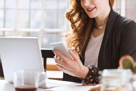 Giovane architetto femminile felice che utilizza smartphone durante la pausa caffè