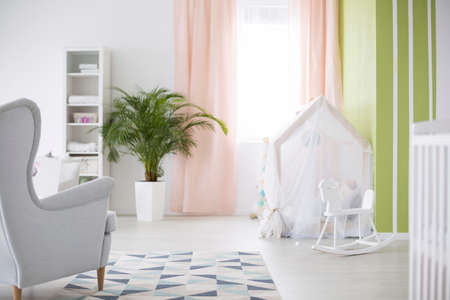 White play tent and rocking horse in cozy baby room Stock Photo