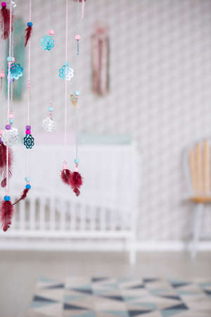 Colorful boho decoration in simple and modest white baby room Reklamní fotografie
