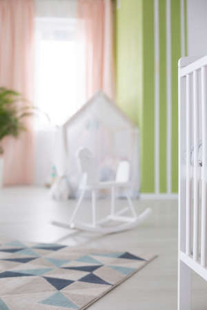 Colorful carpet on wooden floor in baby room