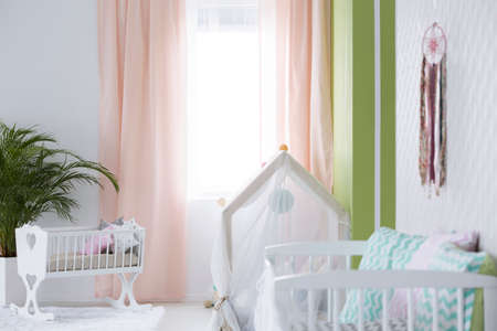 Cozy modern designed baby room with white furniture