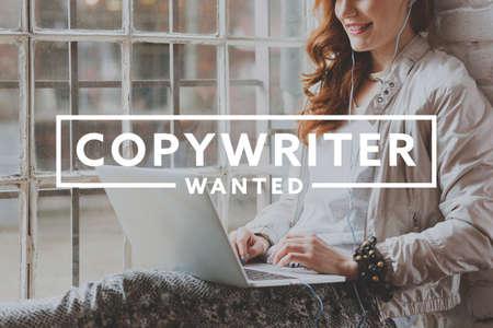 Young smiling beautiful woman working on laptop as freelance copywriter Stock Photo