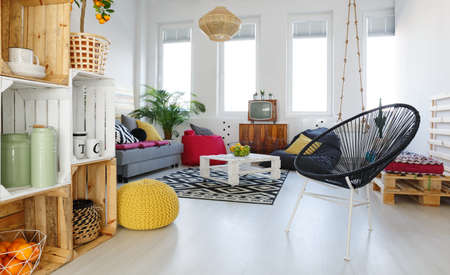 Living room with round chair, yellow pouf, sofa, pallet furniture