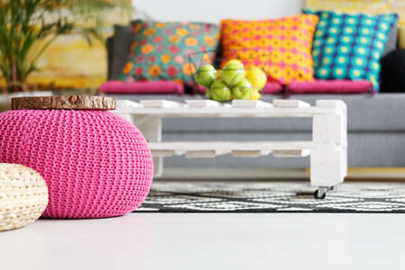 Interior with pink pouf, colorful cushions, grey couch, diy table