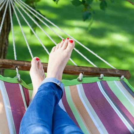Vrouw het ontspannen op een hangmat in tuin Stockfoto
