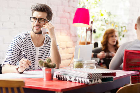 Hipster graphic designer talking on smartphone in trendy coffee shop Stock Photo