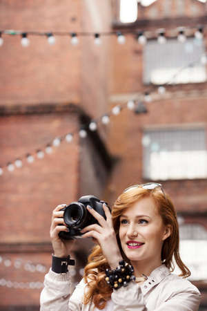 Attractive ginger woman taking pictures working as freelance photographer Stock Photo