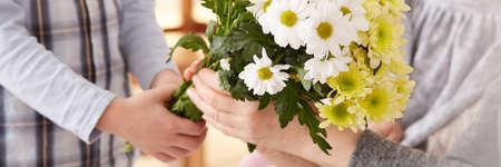 彼の祖母に花をあげる少年のクローズ アップ