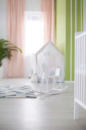 Spacious white room with rocking horse designed for baby Stock Photo