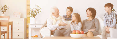 Group of young kids sitting on a sofa with their grandparents 스톡 콘텐츠 - 122034895