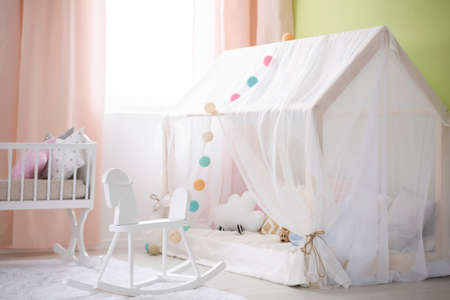 Cozy white place for baby with tent, cradle and rocking horse