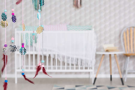 Colorful dreamcatcher in white modern baby room with cradle