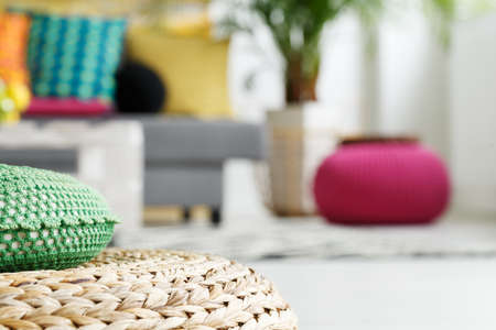 Interior with rattan cushion, pink and green pouf, close up Stock Photo