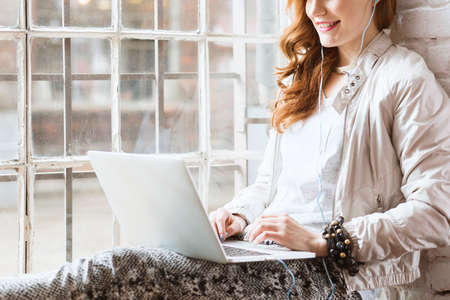 Female graphic designer artist using laptop in windowsill at cafe
