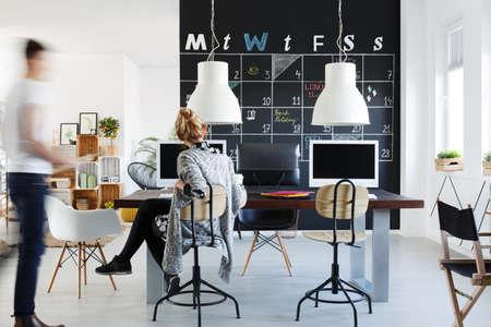 나무 책상, 의자 및 컴퓨터가있는 심플한 스타일의 사무실