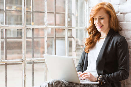 Happy young freelance copywriter woman using laptop sitting on windowsill