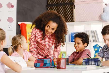 Glimlachende vrouwelijke leraar die les verklaart aan de leerlingen