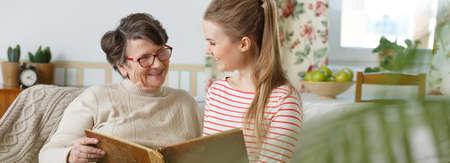 Smiling grandma and granddaughter watching family photo album