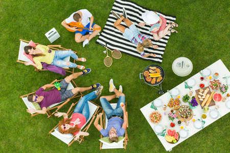 午後を過ごすお友達のグループ、庭でのバーベキュー