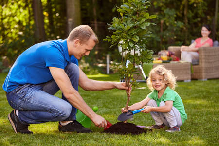 Happy father and his little son planting a small tree Фото со стока