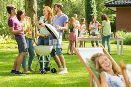 ガーデン パーティーにバーベキューを楽しんで 2 つ若いカップル