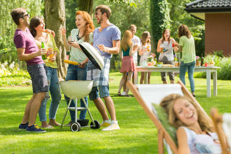 Two young couples having fun with barbecue on a garden party
