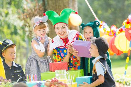 Femme comme un clown donnant des cadeaux pour les enfants sur une fête Banque d'images - 79393003