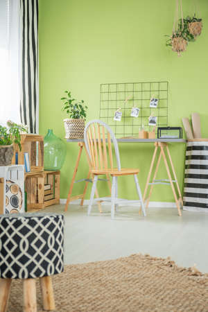 Comfortable room with metal chair and green wall