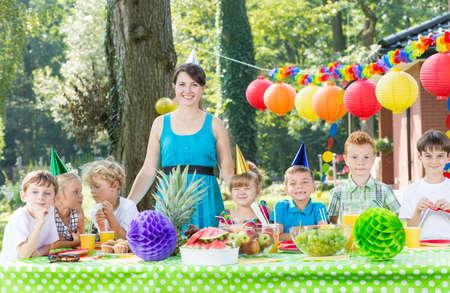 Femme en tant qu'animateur s'amuser avec les enfants lors d'une fête de jardin Banque d'images - 79392602