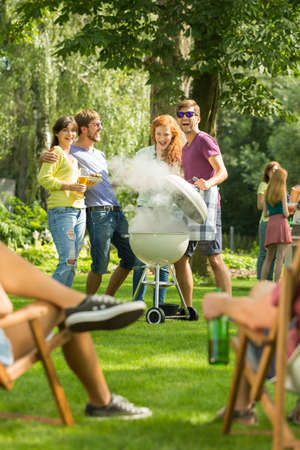 Two young couples watching the food on the barbecue