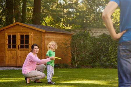 Familie spelen met een frisbee in de tuin Stockfoto