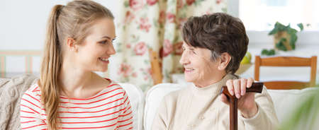 Young woman and her grandma sitting on a sofa and smiling at each other