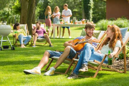 彼のガール フレンドにギターを弾く若いハンサムな男