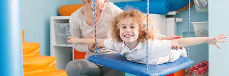 Smiling child exercising on a therapy swing Banco de Imagens