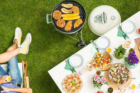 Tasty food on a white table in the garden next to barbecue Stock Photo - 79391424