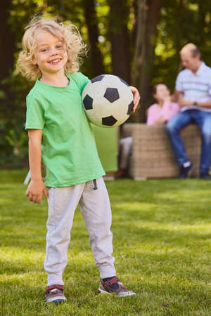 upbringing: Sweet little son holding a football ball in the garden Stock Photo