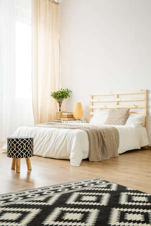 Double bed in cozy modern bedroom full of light