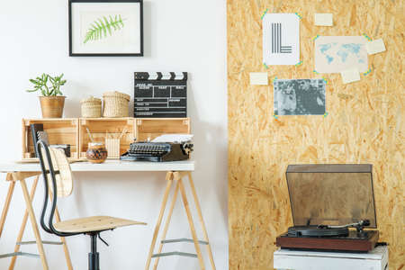 Modern room with desk, record player, posters and osb board Stock Photo