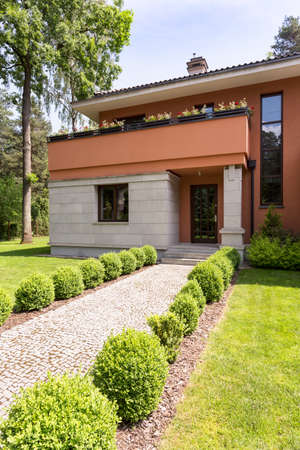 Contemporary house exterior with gravel pathway in garden