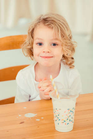 Little boy sitting at the table with spilled milk Stock Photo