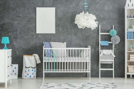 Witte babybed in een kamer met grijze muur en een mintlamp Stockfoto