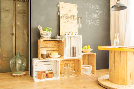 Wooden crates with bottles and plates against blackboard wall