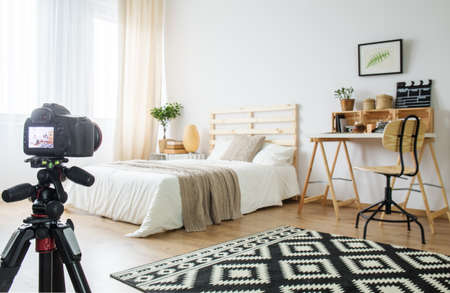 Camera on a tripod in modern bedroom interior