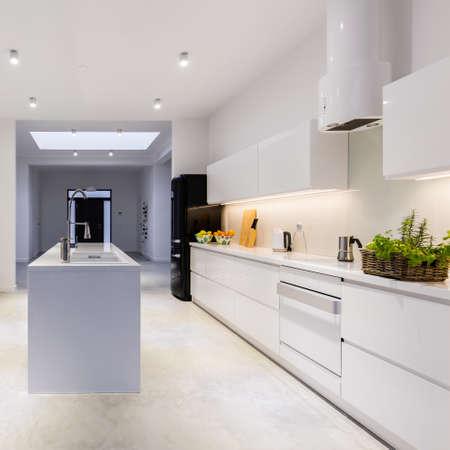 Moderne, lichte keuken met kookeiland in het midden en witte eenvoudige kasten Stockfoto