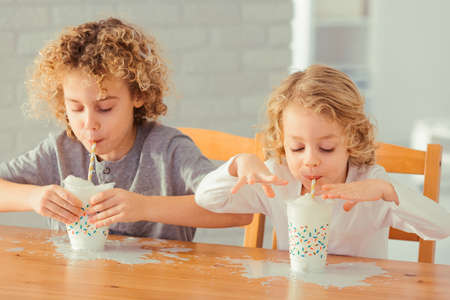 Two little boys spilling milk on the kitchen table